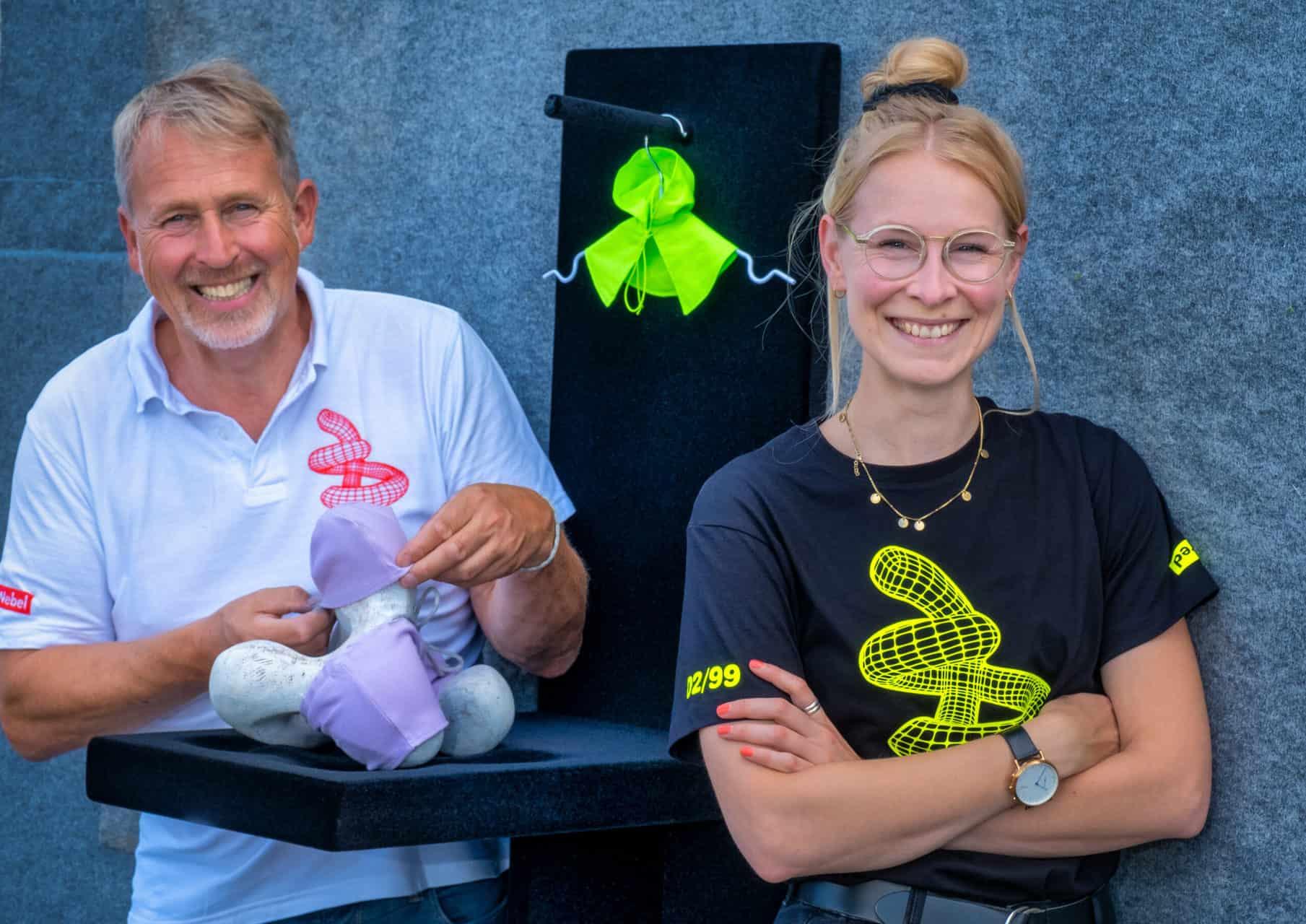 Pressefoto Manfred Webel mit Modemacherin Laura Schlütz, die für die Bewegungsskulptur Quattroporte (hier das kleine Zirbenholzmodell)eine Modekollektion angefertigt hat